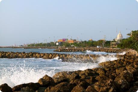 Petites vagues qui s'éclatent sur les rochers avec un bâtiment du centre-ville de Carthagène en fond de photo