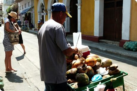 homme découpant une noix de coco fraîche sur son charriot dans une rue de Carthagène